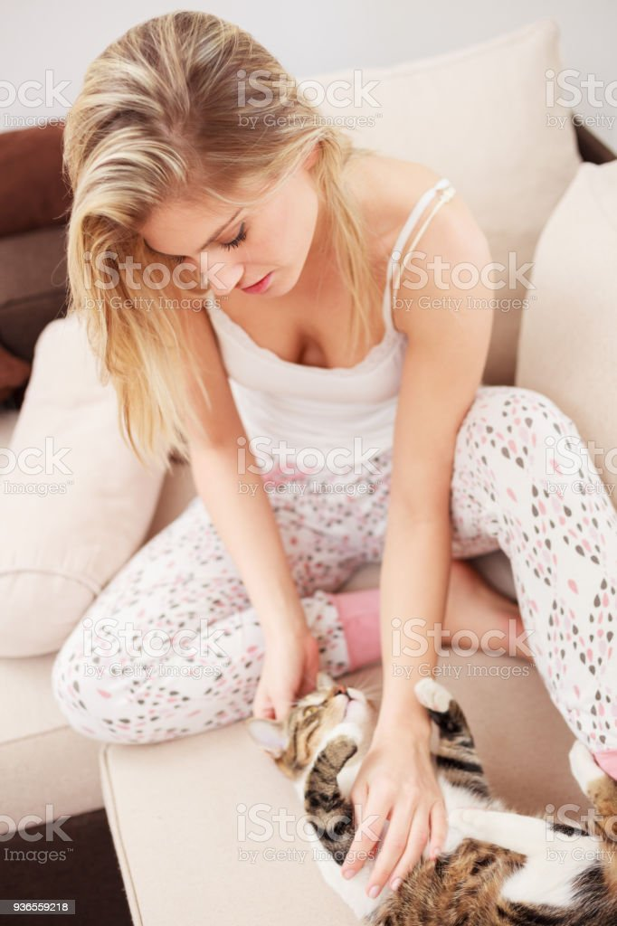 e380788fb3 Mujer joven en pijama acariciando a su gato foto de stock libre de derechos