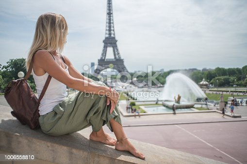 One girl at the Eiffel Tower in Paris during Springtime in sunny day. People travel discovery city concept Young caucasian woman tourist in Paris