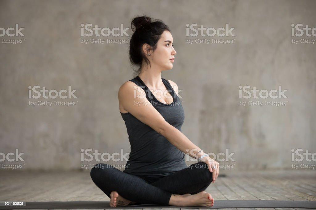 Young woman in Parivrtta Sukhasana pose stock photo