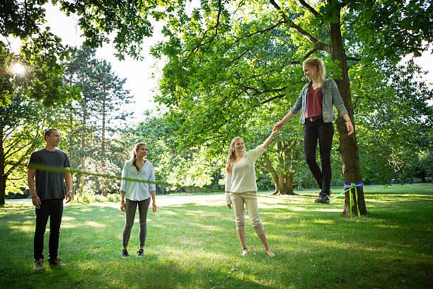 junge frau im park und balancierst auf der slackline - slackline stock-fotos und bilder