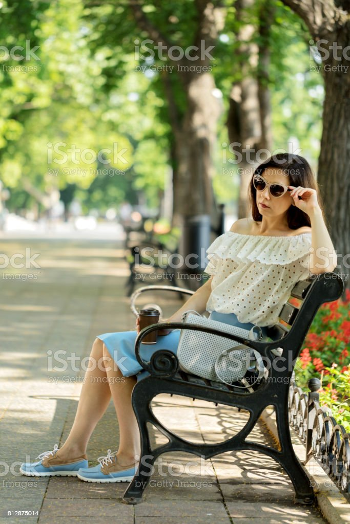 Young woman in park on bench drinking coffee. stock photo