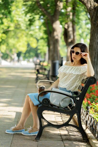 junge frau im park auf bank kaffee trinken. - rüschenbluse stock-fotos und bilder