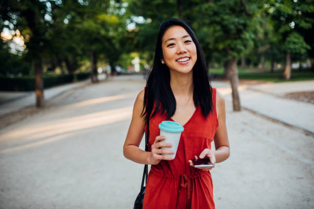 Young woman in park using smartphone stock photo