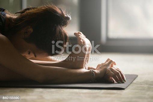 istock Young woman in paschimottanasana pose, studio floor background, closeup 840155590