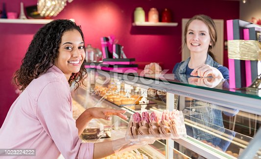 istock Young woman in pastry shop helping customer 1023224222