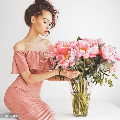 Lifestyle photo of beautiful young woman with pink peonies. Bouquet as gift. Emotions of happiness and joy. Valentines day. Mothers day