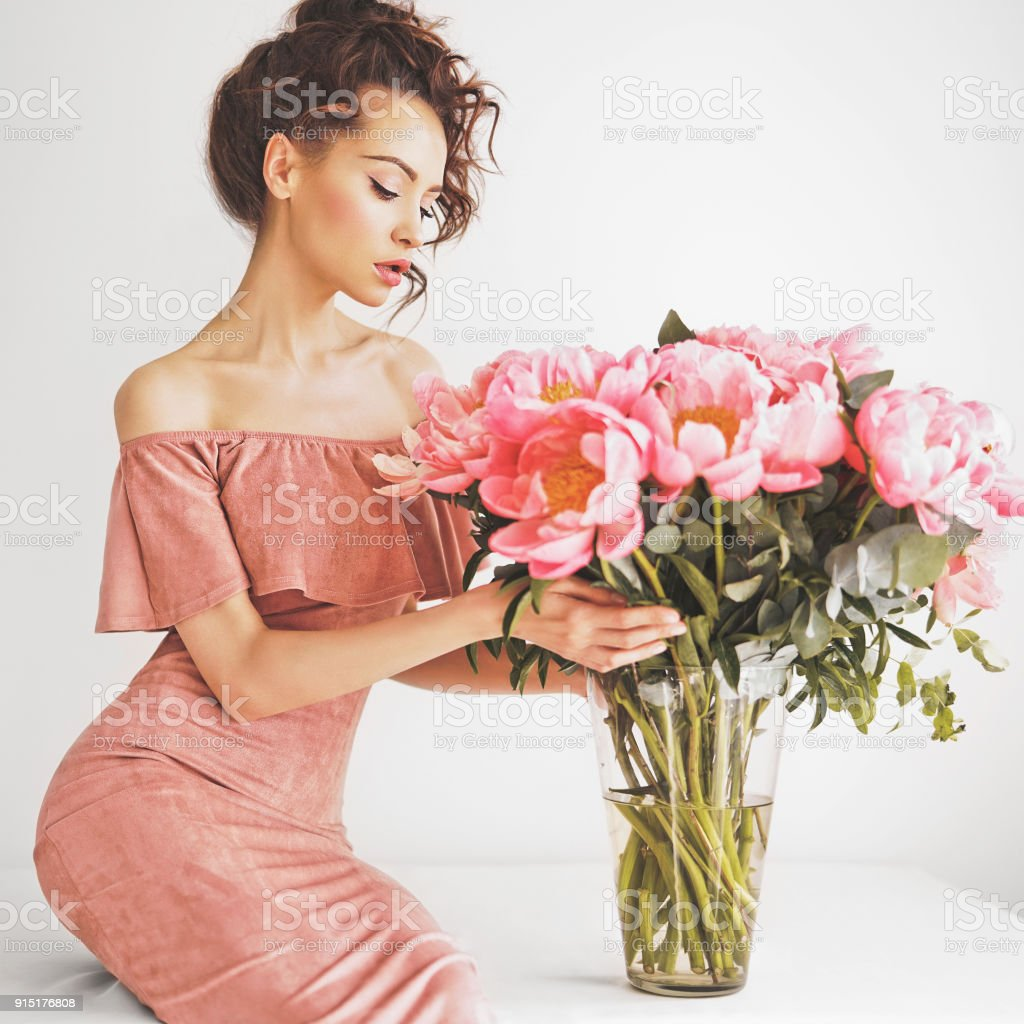 Young woman in pink dress with pink peonies stock photo