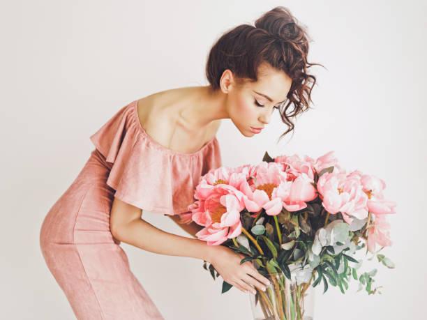 junge frau im rosa kleid mit rosa pfingstrosen - soup_studio stock-fotos und bilder