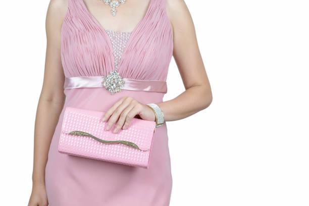 junge frau in rosa elegantes damenkleid rosa luxushandtasche isoliert auf weißem hintergrund halten. mode-accessoires. - enge kleider stock-fotos und bilder