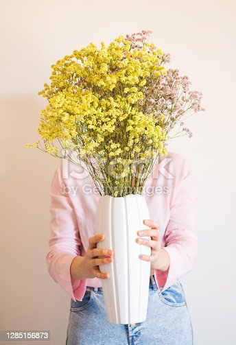 Young woman in pink shirt with vase of dried colorful flowers