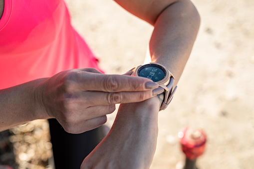 A young woman in pink sports equipment running in nature looks at her smartwatch.
