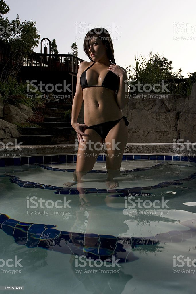 Beautiful girl stands at the edge of a pool.