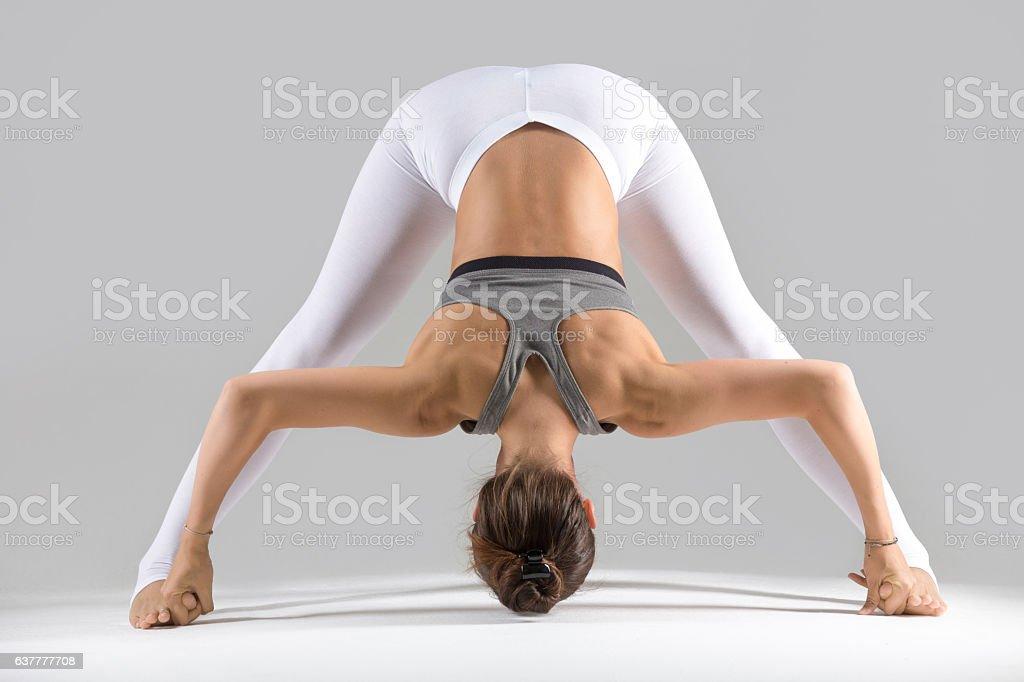 Young woman in Prasarita Padottanasana pose, grey studio backgro stock photo