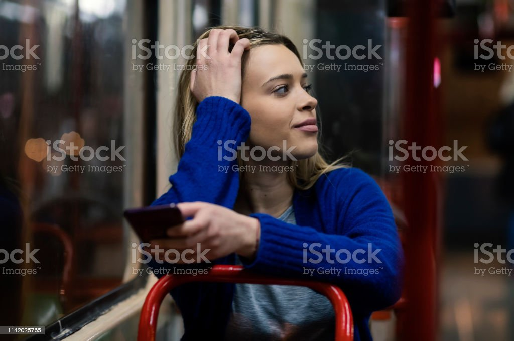 Young woman riding in public transportation and using mobile phone