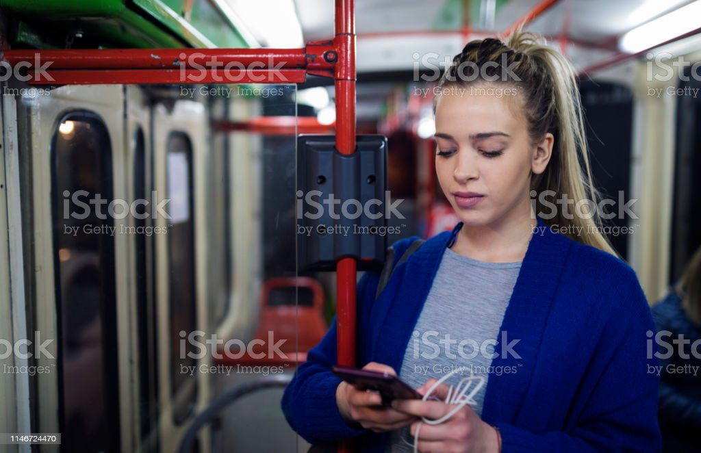 Young woman riding in public transportation at night. Listening music...