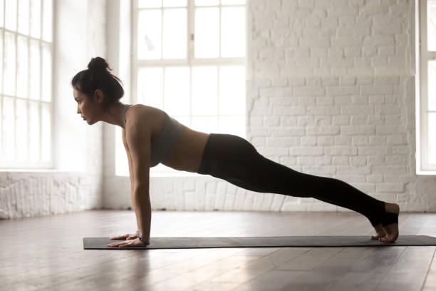 young woman in push ups or press ups pose, studio - peso mosca foto e immagini stock