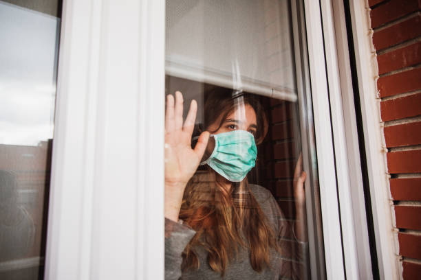 Young woman in quarantine wearing a mask and looking through the window stock photo
