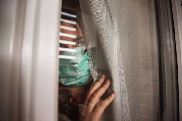 Young woman in quarantine wearing a mask and looking through the window A young woman in quarantine wearing a mask and looking through the window quarantine stock pictures, royalty-free photos & images