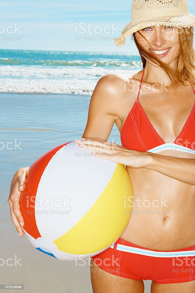 Young woman in red bikini holding a beach ball royalty-free stock photo