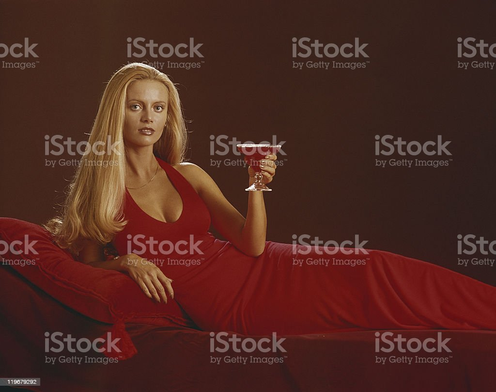 Young woman in red dress holding glass of drink, portrait royalty-free stock photo