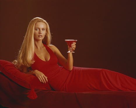 Young woman in red dress holding glass of drink, portrait
