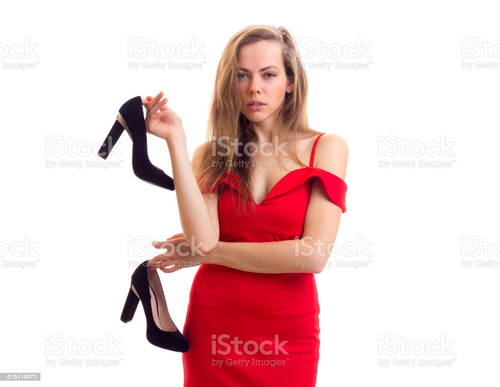 Young woman in red dress holding shoes photo libre de droits
