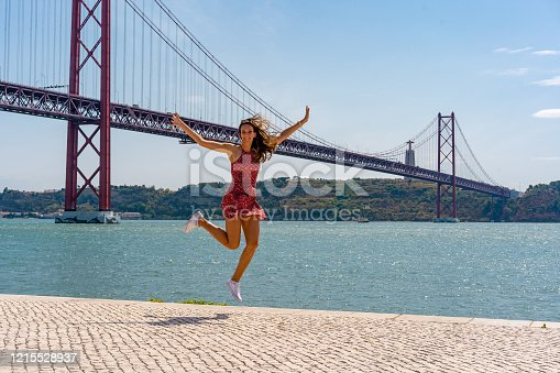 istock Young woman in red dress jumping in front of the famous bridge in Lisbon 1215528937
