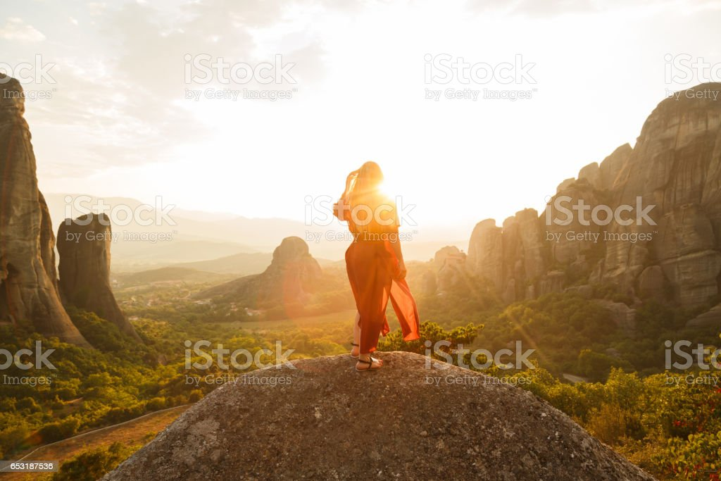 Young woman in red dress looking at majestic sunset in Meteora valley, Greece stock photo