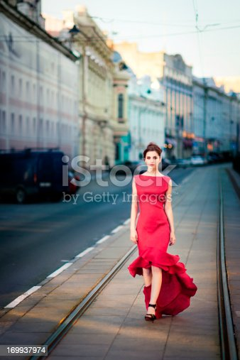 Young brunette woman wearing remarkable red dress is calmly walking on city streets and looking into camera.