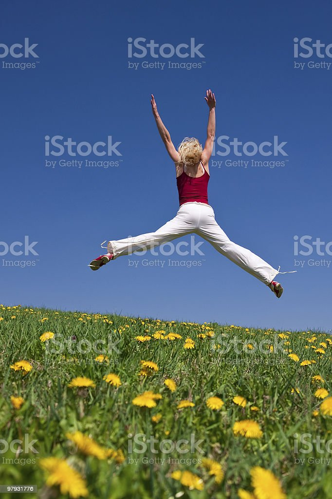 young woman in red outfit having fun on meadow royalty-free stock photo