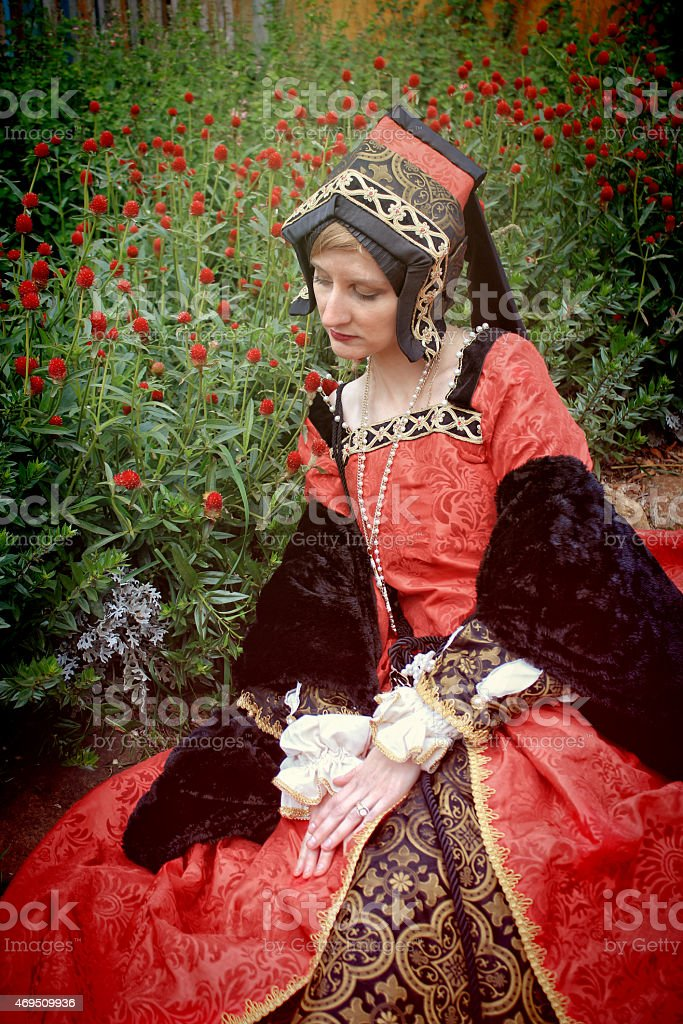 Young Woman in Red Renaissance Dress Sitting Beside Flower Garden stock photo