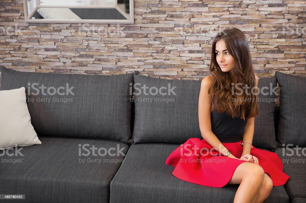 Jovem mulher em vermelho Saia na black sofá - foto de acervo