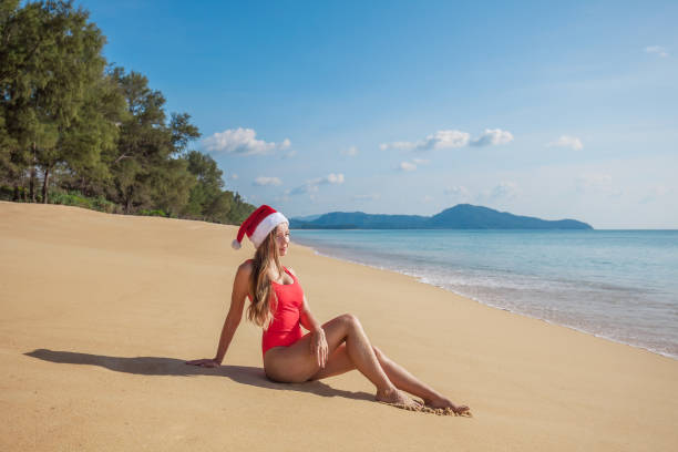 330c87605d Young Woman In Red Swimsuit And Santa Claus Hat Sitting On The Wide Empty  Tropical Beach Stock Photo   More Pictures of Adult