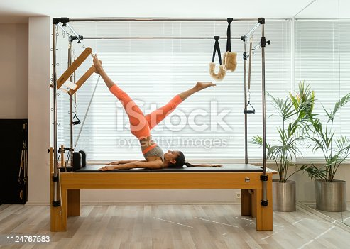 Young woman in reformer fitness exercise