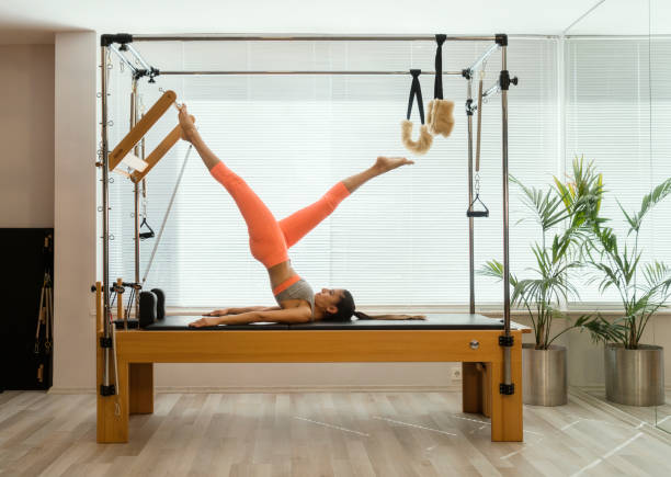 young woman in reformer fitness exercise - metodo pilates foto e immagini stock