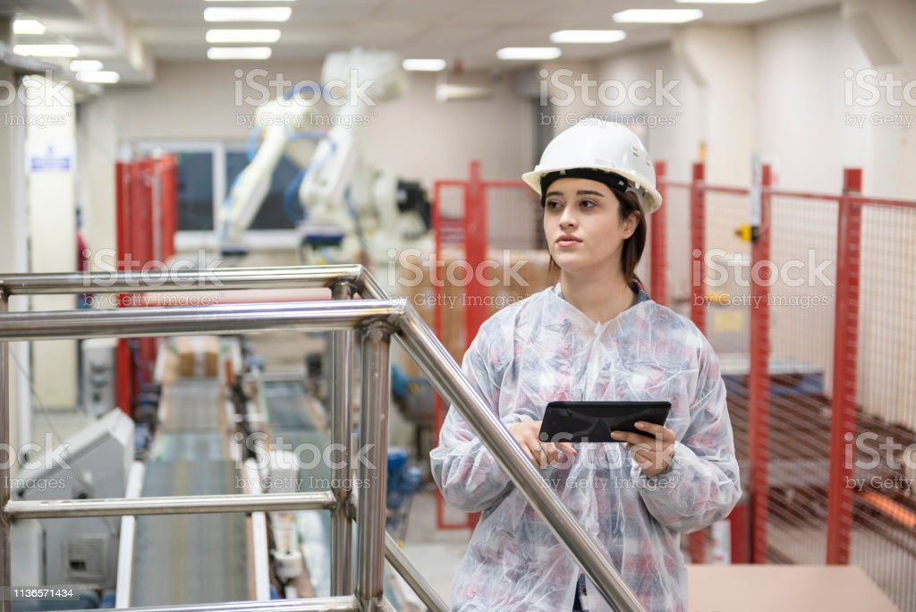 Young woman in robotic packaging line.