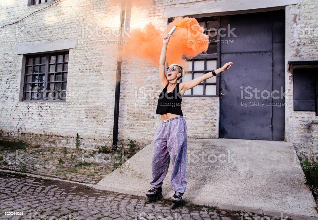 Mujer joven en patines con bomba de humo - foto de stock