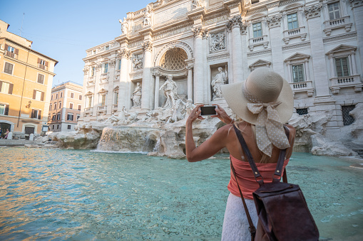 Young woman in Rome enjoying travel in Italy and capturing a photo of the Trevi fountain using her smart phone