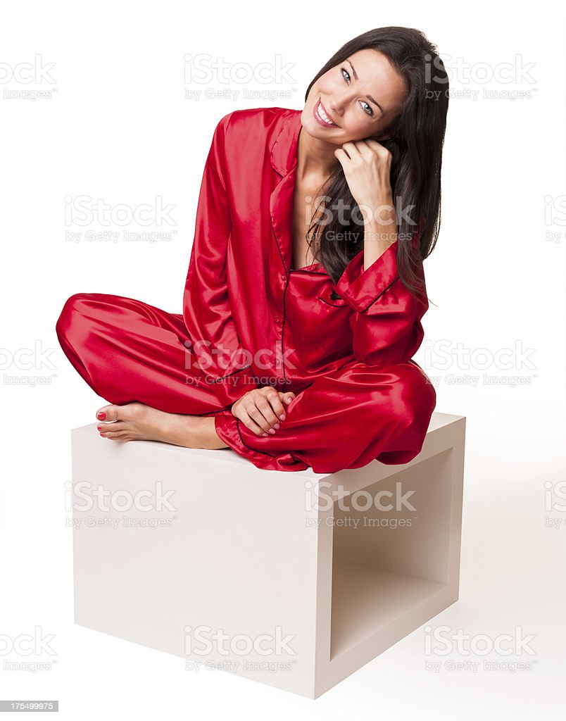young woman in satin pajamas seated isolated on white. Black Bedroom Furniture Sets. Home Design Ideas