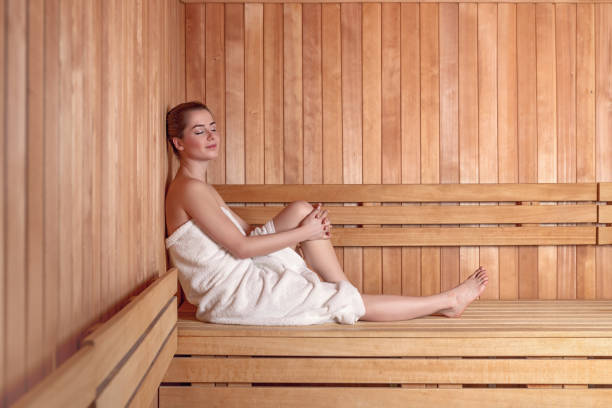 Young woman in sauna Side view full length portrait of young woman smiling sitting on wooden sofa bench in sauna wrapped in white towel, with hair in donut bun sauna stock pictures, royalty-free photos & images