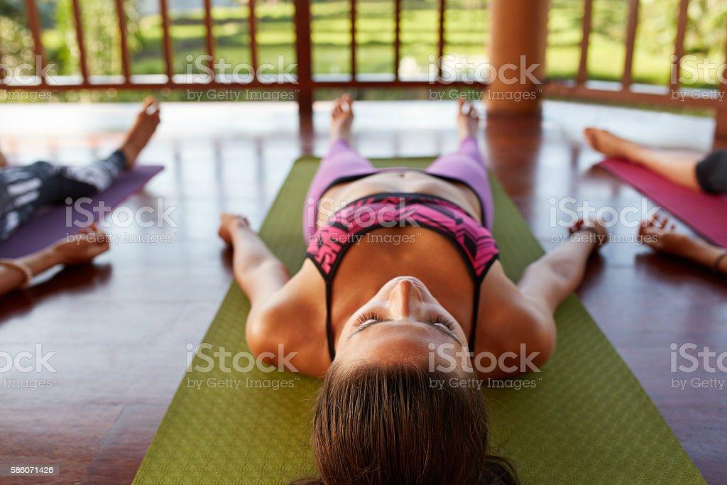 Young woman in savasana at yoga class stock photo