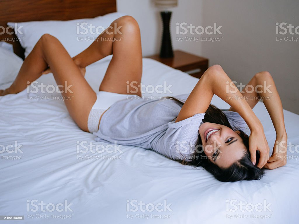 Young woman in seductive pose laughing on bed stock photo