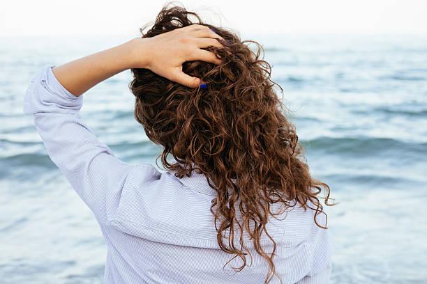 junge frau in shirt mit blick auf das meer - haare ohne lockenstab wellen stock-fotos und bilder