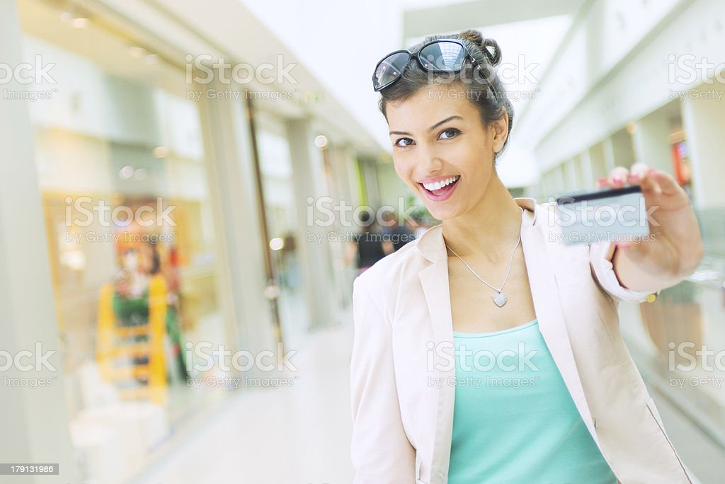 Young woman in shopping center holding out a credit card stock photo