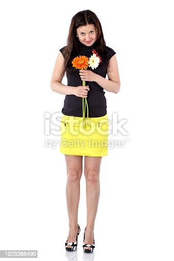 Young woman in short yellow skirt with gerberas, full body, tilting her head forward