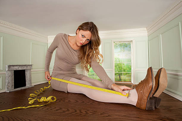 young woman in small room measuring her leg - trap house stock pictures, royalty-free photos & images