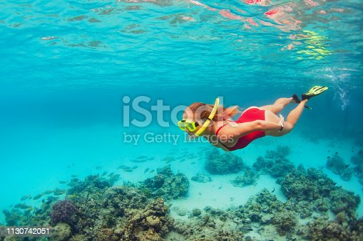 831127716 istock photo Young woman in snorkeling mask dive underwater with tropical fishes 1130742051