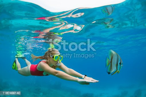 831127716 istock photo Young woman in snorkeling mask dive underwater with tropical fishes 1182466140