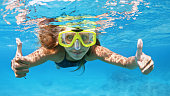 istock Young woman in snorkeling mask dive underwater with tropical fishes 1223330882