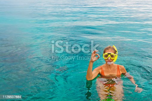 577645320 istock photo Young woman in snorkeling mask showing divers sign OK 1129537884